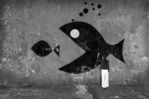 businesswoman drawing  big fish  on the wall