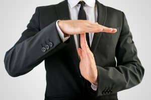 Close up Businessman in Black Suit Showing Time Out Sign, Isolated on Gray Background.