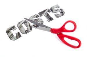 Red handled scissors cutting the word COSTS made from one hundred dollar bills on a white background